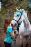Cavalier de fille et son cheval à reposer près de l'écurie après la monte Image libre de droits