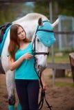 Cavalier de fille et son cheval à reposer près de l'écurie après la monte Photographie stock libre de droits