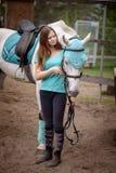 Cavalier de fille et son cheval à reposer près de l'écurie après la monte Photo libre de droits