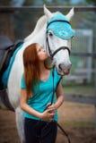 Cavalier de fille et son cheval à reposer près de l'écurie après la monte Photographie stock