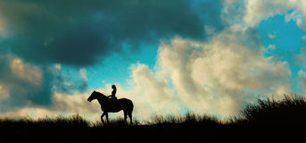 Cavalier de horseback au-dessus de ciel bleu sur un bâti Photo stock