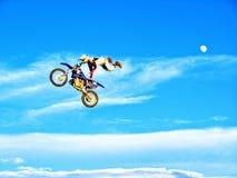 Cavalier de motocyclette de FMX accomplissant des cascades contre le contexte d'un ciel bleu avec les nuages et la lune Image libre de droits