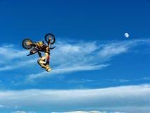 Cavalier de motocyclette de FMX accomplissant des cascades contre le contexte d'un ciel bleu avec les nuages et la lune Photo stock