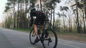 Cavalier de vélo sprintant hors de la selle comme parc de la formation de recyclage Équipement noir de port Muscles forts de jamb banque de vidéos