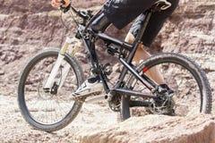 Cavalier handicapé de vélo de montagne entre les roches Photo stock