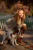Cavalier King Charles Spaniel dog and a girl are together in the park enjoying beautiful autumn day. Beautiful dog Cavalier King Charles Spaniel, white with red stock photography