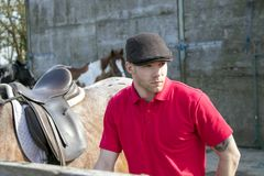 Cavaliere bello del cavallo in camicia di polo rossa e flatcap che sta accanto al suo cavallo sellato Fotografie Stock Libere da Diritti