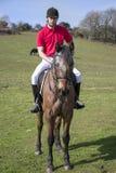 Cavaliere bello del cavallo maschio a cavallo con le culatte bianche, gli stivali neri e la camicia di polo rossa nel campo verde Immagini Stock Libere da Diritti