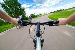 Cavaliere che conduce bicicletta su una strada asfaltata Fotografia Stock