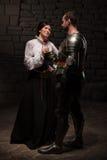 Cavaliere che dà una rosa a signora Fotografia Stock