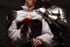 Cavaliere che dà una rosa a signora immagine stock