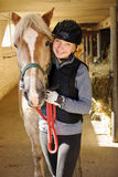 Cavaliere con il cavallo in stalla Immagini Stock