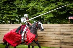Cavaliere corazzato a cavallo che fa pagare in una giostra fotografia stock