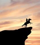 Cavaliere del cavallo sulla siluetta della scogliera Immagine Stock