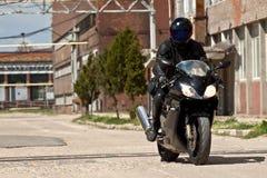 Cavaliere del motociclo con l'attrezzatura nera completa Fotografia Stock