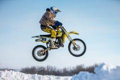 Cavaliere del primo piano su un salto del motociclo sulla montagna Cielo blu Fotografia Stock