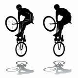 Cavaliere di salto della siluetta su una bici Fotografia Stock