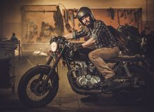Cavaliere ed il suo motociclo d'annata del caffè-corridore di stile Immagini Stock