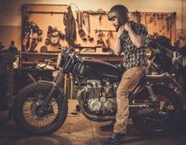 Cavaliere ed il suo motociclo d'annata del caffè-corridore di stile Fotografia Stock