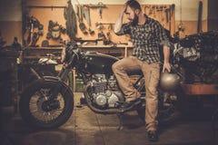 Cavaliere ed il suo motociclo d'annata del caffè-corridore di stile Immagini Stock Libere da Diritti