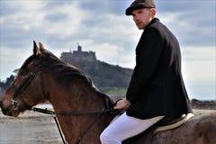 Cavaliere maschio bello sul cavallo con flatcap dentro di vecchio castello Immagini Stock Libere da Diritti