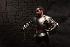 Cavaliere medievale che posa con la spada in una pietra scura fotografia stock libera da diritti