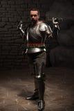 Cavaliere medievale che posa con la spada in una pietra scura immagine stock libera da diritti