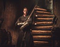 Cavaliere medievale nell'interno antico del castello Immagini Stock