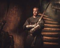 Cavaliere medievale nell'interno antico del castello Fotografie Stock Libere da Diritti