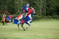 Cavaliere rosso e blu in carica Fotografia Stock Libera da Diritti