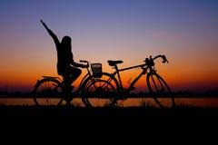 Cavalieri che ciclano contro il tramonto in siluetta con i lotti di spazio negativo e del cielo drammatico Fotografia Stock