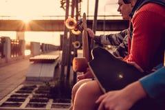 Cavalieri del pattino che si rilassano su un banco dopo la guida al tramonto Immagine Stock