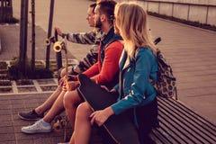 Cavalieri del pattino che si rilassano su un banco dopo la guida al tramonto Fotografia Stock Libera da Diritti