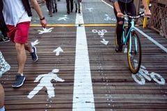 Cavalieri della bicicletta e del pedone che dividono i vicoli della via con la segnaletica stradale nella città Fotografie Stock