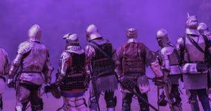 Cavalieri medievali messi contro un fondo ultravioletto fotografie stock