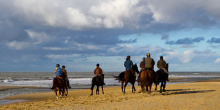 Cavaliers de Horesback sur la plage Photo stock