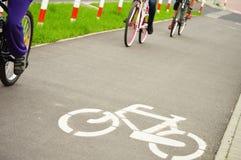 Cavaliers de panneau routier et de vélo de bicyclette Photos libres de droits