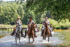 Cavaliers et chevaux traversant la rivière Semois près de Laferet, Belgique photos libres de droits