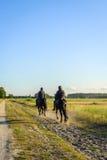 Cavaliers foncés vers la fin du soleil de soirée Image stock