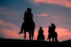 Cavallerizzi nomadi di guida sul tramonto Fotografia Stock Libera da Diritti
