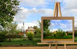 Cavalletto con un paesaggio rurale dell'acquerello della pittura con il villaggio GA Immagine Stock