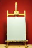 Cavalletto della pittura con tela bianca per testo alla luce drammatica Fotografie Stock