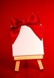 Cavalletto di legno con tela in bianco su fondo rosso immagine stock libera da diritti