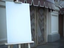 Cavalletto di legno con una tela in bianco vicino al caffè Fotografia Stock
