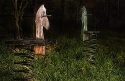 Cavalli a dondoli di legno della primavera alla notte Immagine Stock