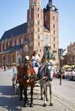 Cavalli sul servizio quadrato a Cracovia Immagine Stock Libera da Diritti