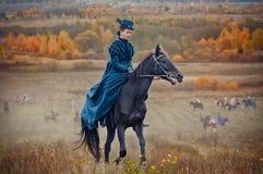 Cavallo-caccia con i cavalieri nell'abitudine di guida fotografie stock libere da diritti