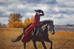 Cavallo-caccia con i cavalieri nell'abitudine di guida Immagine Stock Libera da Diritti