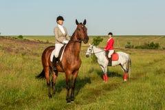 A cavallo cavalieri Due donne attraenti montano i cavalli su un prato verde Fotografie Stock