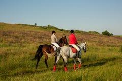 A cavallo cavalieri Due donne attraenti montano i cavalli su un prato verde Fotografia Stock Libera da Diritti